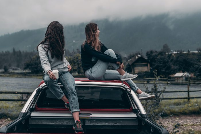 two-women-sitting-on-vehicle-roofs-2409681