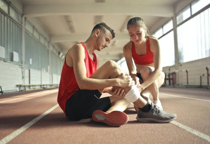 woman-helping-sportsman-with-injury-during-cardio-training-3760275