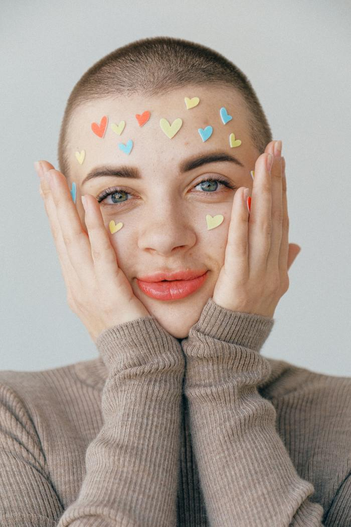 young-positive-woman-with-many-stickers-on-face-3851309