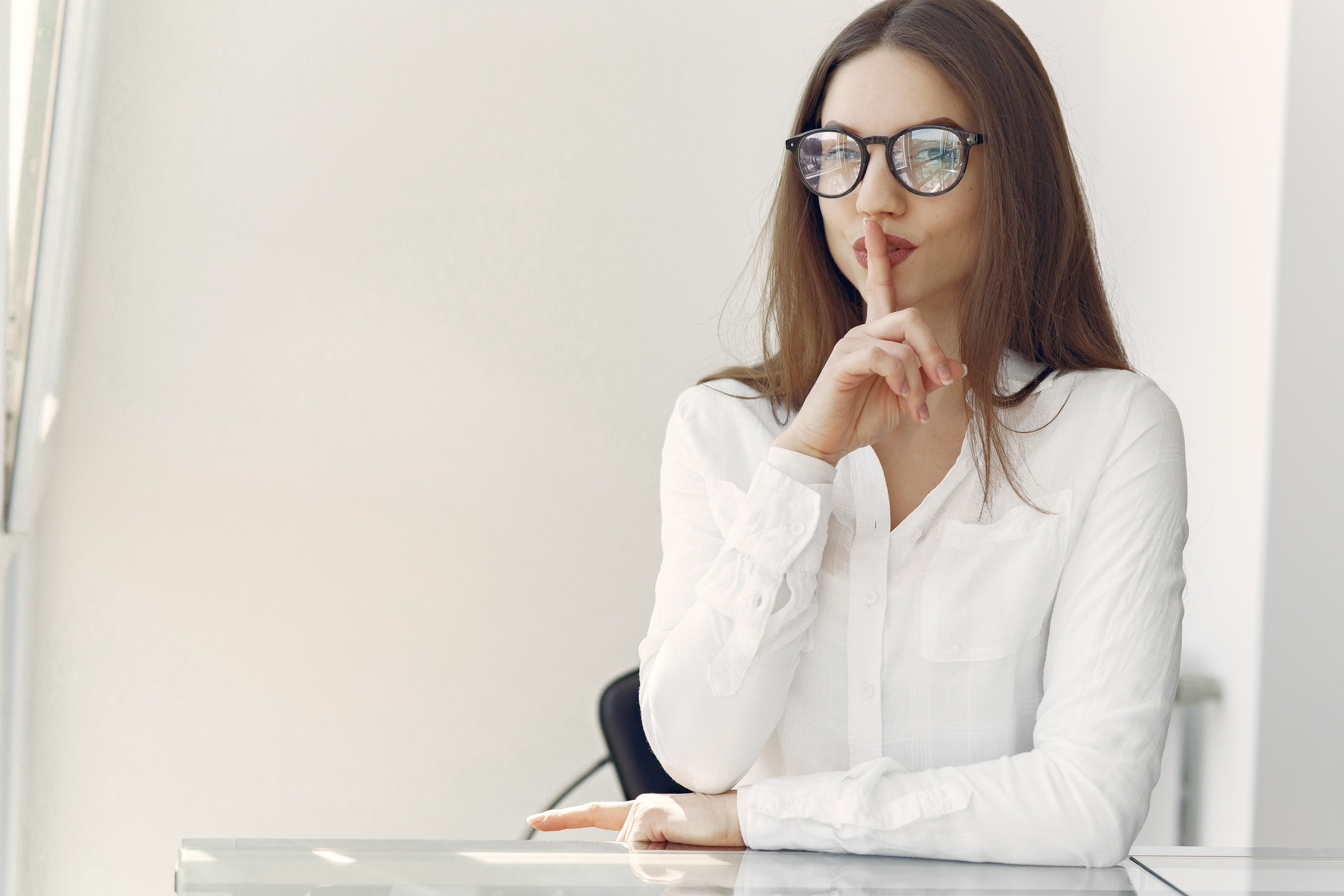 flirty-young-lady-asking-to-keep-secret-sitting-in-office-4149070